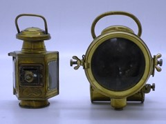 Navigate to Two early brass oil lamps.